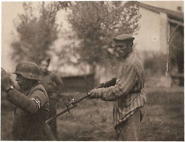 38. A liberated Jew holds a Nazi guard at gunpoint