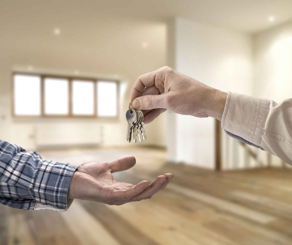 Realtor giving house key to buyer in empty room