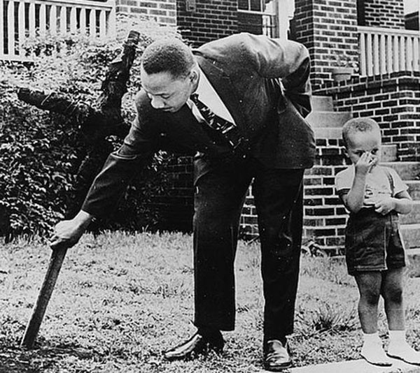 12. Martin Luther King, Jr removes a burned cross from his yard in 1960. The boy is his son.