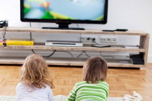 Siblings Lying On Rug While Watching Television At Home