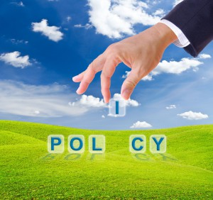 9943550 - business man hand made policy word buttons on green grass meadow