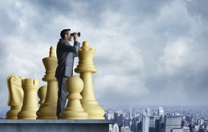 Businessman Standing Among Chess Pieces Looks Through Binoculars