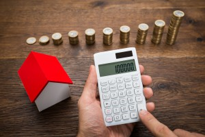 Businessman With Coins And House Model Using Calculator
