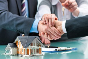 Estate Agent Shaking Hands With Customer After Contract Signatur