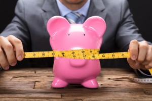 Businessman Squeezing Piggybank With Tape Measure On Table