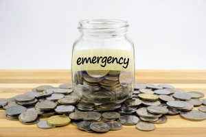 Coins In Glass Container With Emergency Label On Wooden Surface